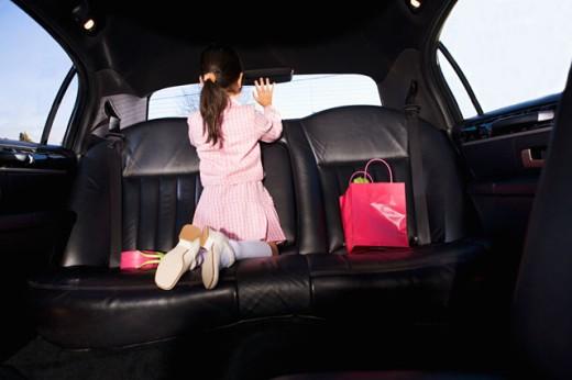 Girl in car waving goodbye : Stock Photo