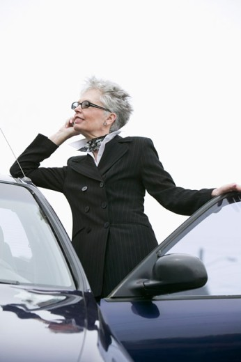 Stock Photo: 1530R-33018 Woman next to car using mobile phone