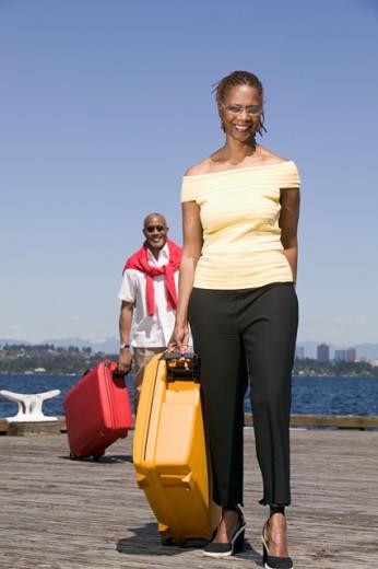 Couple on dock pulling luggage : Stock Photo