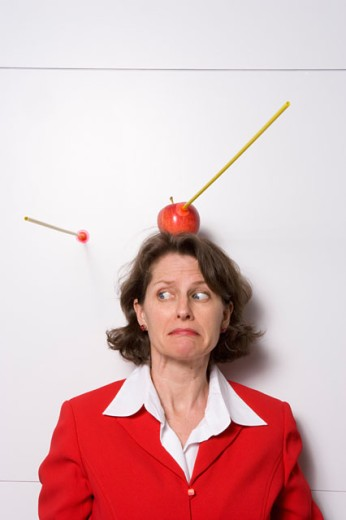Shooting an apple off businesswoman's head : Stock Photo