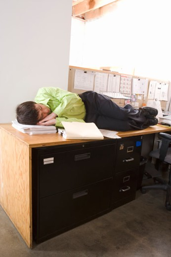 Stock Photo: 1530R-35149 Office worker asleep on desk