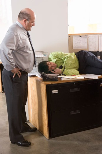 Stock Photo: 1530R-35152 Boss discovering employee asleep on desk