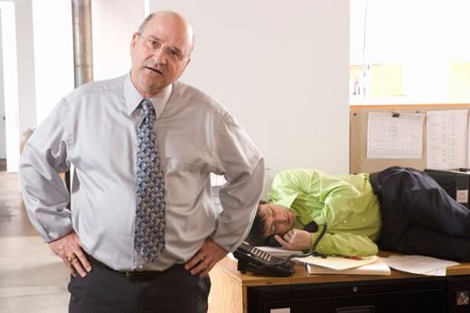 Boss discovering employee asleep on desk : Stock Photo