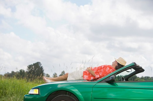 Man resting on a car : Stock Photo