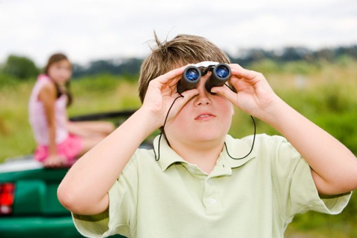 Girl sitting on car as brother uses binoculars : Stock Photo