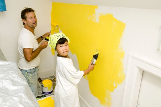 Man and child painting wall : Stock Photo