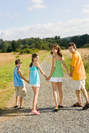 Family holding hands on country road : Stock Photo