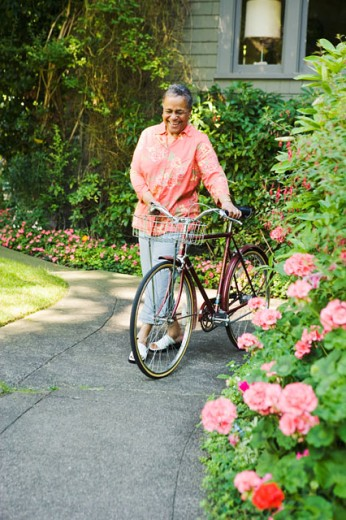 Smiling woman walking her bicycle : Stock Photo
