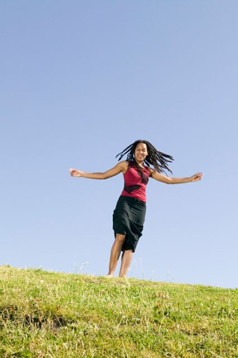 Stock Photo: 1530R-35529 Young woman running on grassy hill