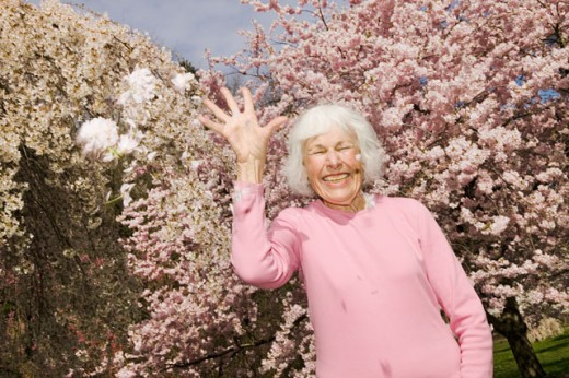 Happy woman throwing flowers : Stock Photo