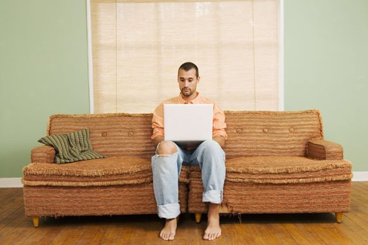 Man sitting on couch using laptop : Stock Photo