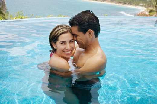 Vacationing couple in swimming pool : Stock Photo