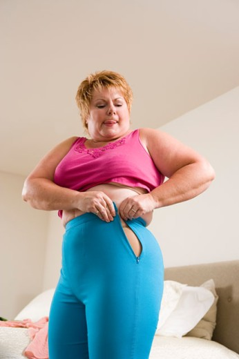 Overweight woman squeezing into tight pants : Stock Photo