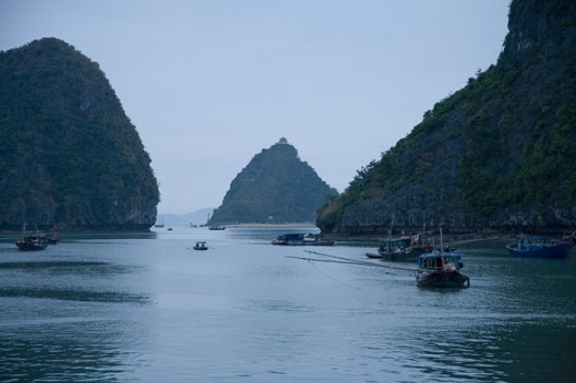 Boats and islands at dusk on Vietnamese bay : Stock Photo
