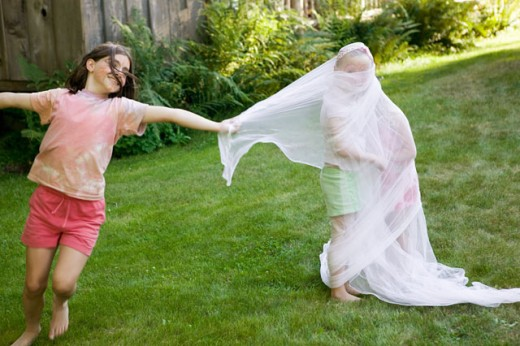 Stock Photo: 1530R-36398 Young girl wrapping friends in fabric