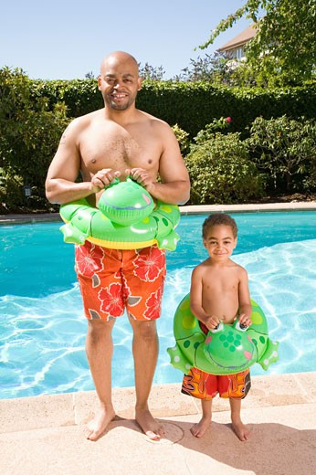 Father and son wearing identical flotation devices by pool : Stock Photo