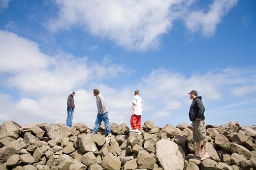 Men walking over rocky terrain : Stock Photo