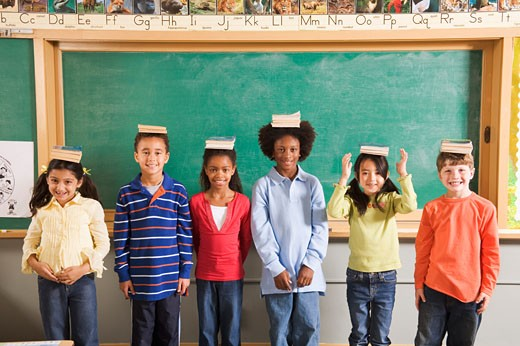 Row of students with books on their heads in classroom : Stock Photo