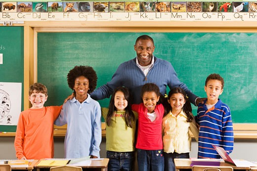 Portrait of male teacher and students in classroom : Stock Photo