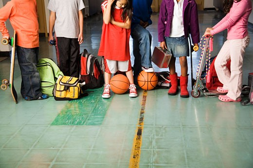 Group of students with sports equipment in hallway : Stock Photo