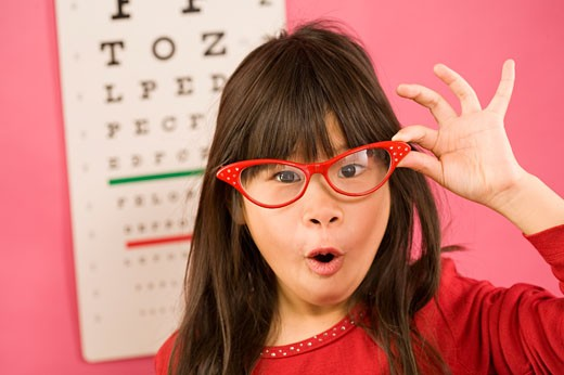 Girl wearing eyeglasses in front of eye chart : Stock Photo