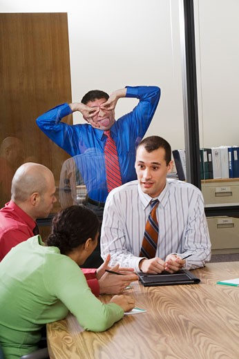 Businessman making faces through glass wall at co-workers : Stock Photo