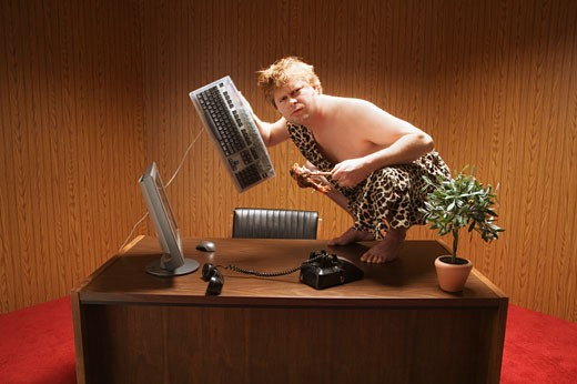 Businessman dressed as caveman crouching on desk : Stock Photo