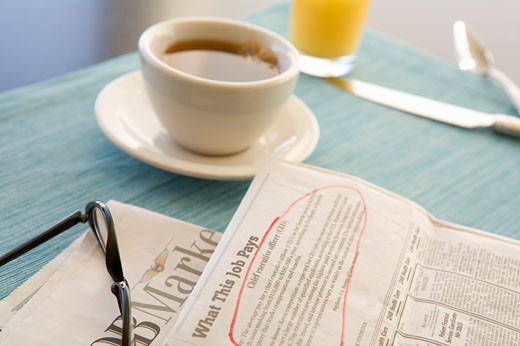 Circled classified ad next to coffee cup : Stock Photo