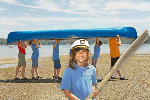 Male camp counselor and children carrying canoe : Stock Photo