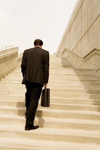 Businessman walking up steps : Stock Photo