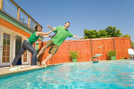 Couple jumping into swimming pool : Stock Photo