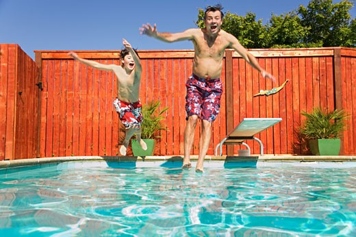 Father and son jumping into swimming pool : Stock Photo