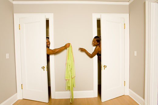 African couple handing clothing between dressing rooms : Stock Photo