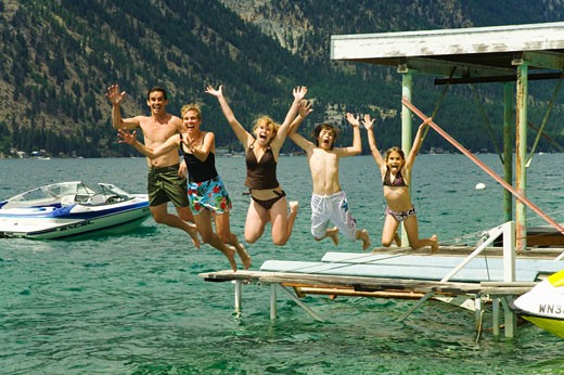 Family jumping into water : Stock Photo