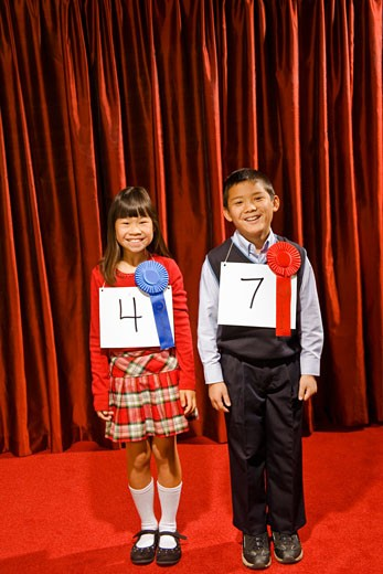 Asian girl and boy wearing prize ribbons on stage : Stock Photo