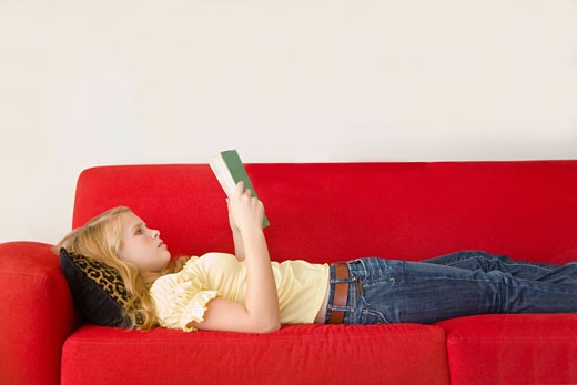 Stock Photo: 1530R-39031 Teenage girl reading on sofa
