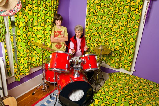 Stock Photo: 1530R-39050 Boy showing grandmother how to play drums
