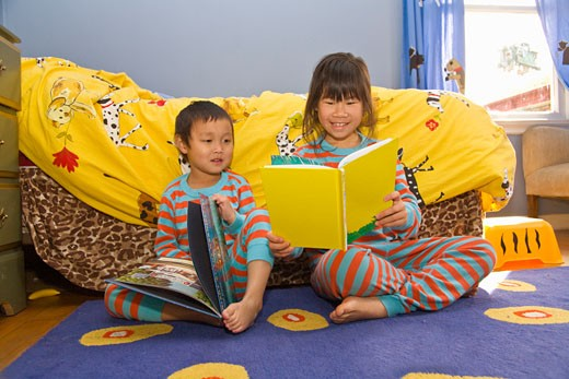 Asian siblings reading books : Stock Photo