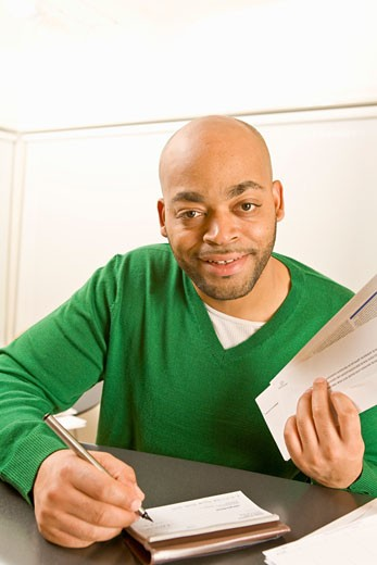 African man writing check : Stock Photo