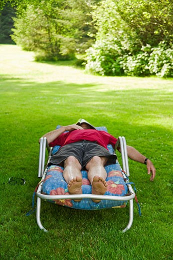 Stock Photo: 1530R-39552 Man with magazine over face relaxing in lounge chair in backyard