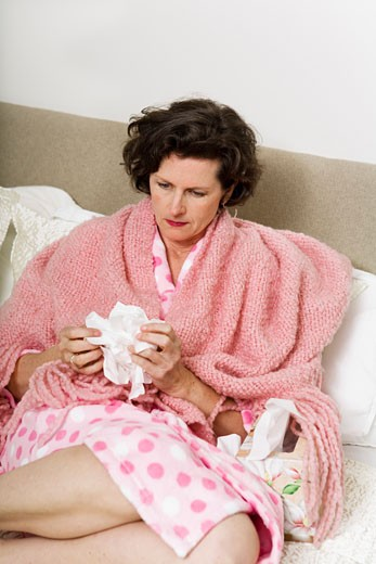 Stock Photo: 1530R-39656 Unhappy woman holding tissue in bed