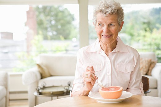 Woman eating a grapefruit : Stock Photo