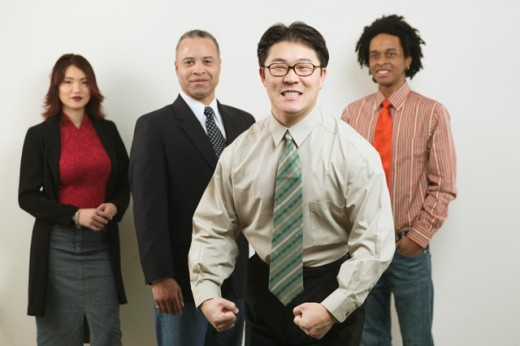 A young businessman flexing his muscles in front of his colleagues. : Stock Photo