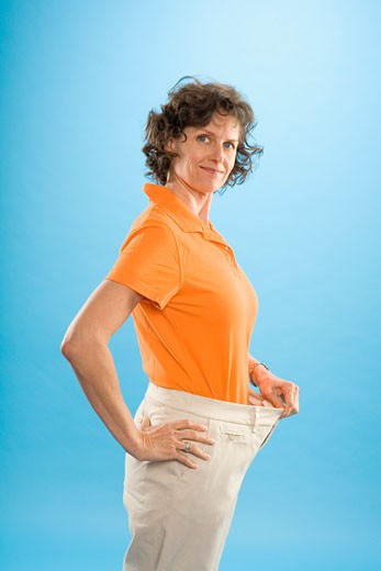 Stock Photo: 1530R-40136 Woman wearing loose pants to show weight loss