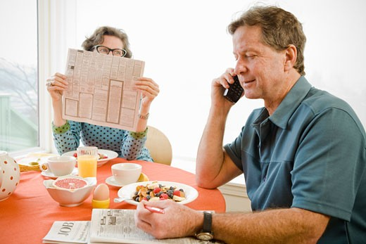 Couple having breakfast and checking newspaper classifieds : Stock Photo