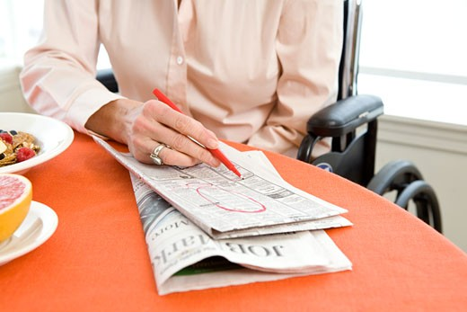 Woman in a wheelchair at breakfast searching classifieds : Stock Photo