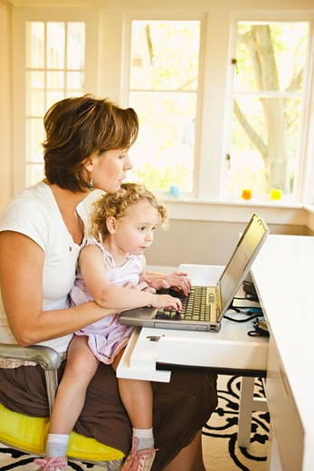 Woman with young child in home office : Stock Photo