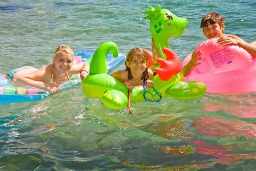 children on floaties in lake : Stock Photo