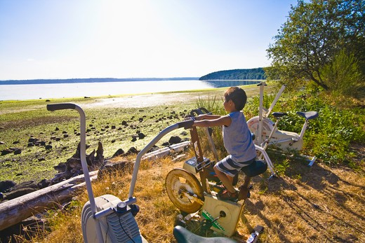Stock Photo: 1530R-40939 boy on exercise bike next to beach