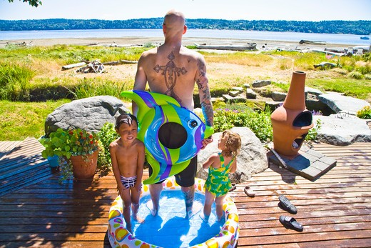 Stock Photo: 1530R-40941 man with kids in wading pool near beach